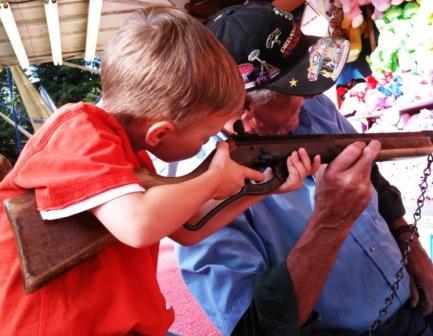 A future NRA member tries his hand at a fun gun game.