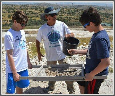 Spencer Serels, Avi Kaner and Jonathan Kaner sift through artifacts, on an archaeological dig.
