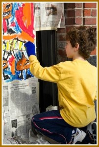 Eytan painting a store window for Halloween
