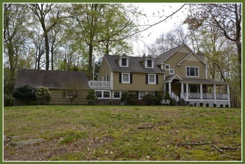 """The """"Fleming House""""  just to the north of the Brodies'. The deck over the original garage remains, but the garage has been converted  into living space, and a new garage added (left). The porch, dormer and new gables effectively camouflage the original '50s split-level."""