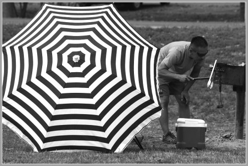 """Man Barbecuing Next to Black and White Umbrella"" -- Larry Silver, 2014."