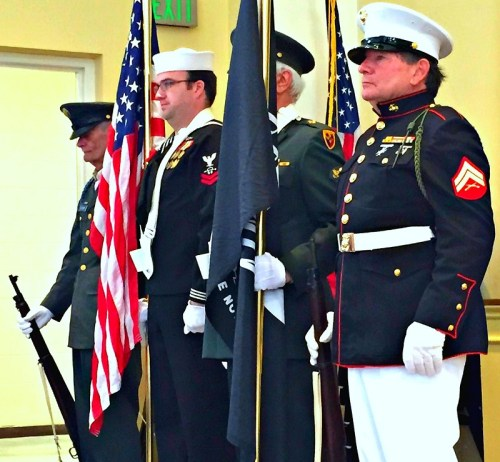 The color guard stands stock still, at attention.