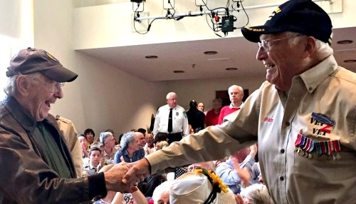 Grand marshal Joe Schachter asked all the veterans in the auditorium to stand. Two former comrades shook hands.
