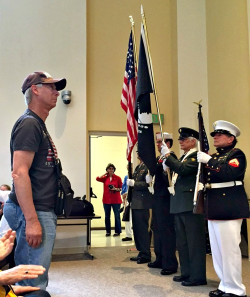 "Navy veteran John Brandt stands as the Staples High School band plays ""Anchors Aweigh""..."