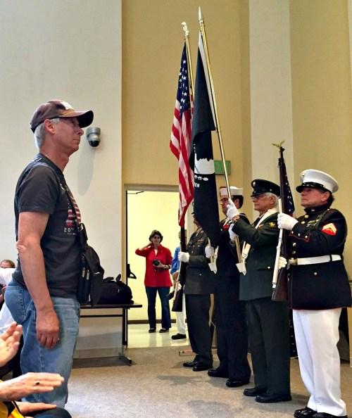 "Navy veteran John Brandt stands as the Staples High School band plays ""Anchors Aweigh""..."