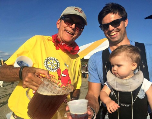 Homes With Hope CEO and Lobster Fest volunteer Jeff Wieser pours a beer for 1-year-old Andy Wolf. Her dad, Jim, looks on amused.