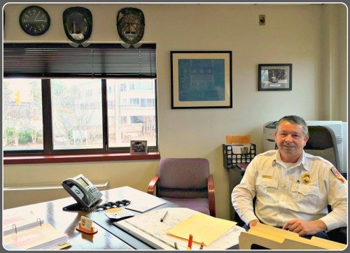 Westport Fire Department chief Andrew Kingsbury, in his office. On the left -- above the windows facing the Post Road -- are souvenir fire helmets.