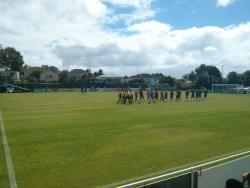 Zwei Mannschaften betreten einen Fußballplatz