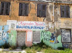 """Leslie writes: """"The buildings throughout Curacao are beautiful – even when they are crumbling. Many commercial buildings are covered with painted advertisements for beauty salons, supermarkets and restaurants. This [roving] barber shop was tagged with the words """"no pichi aki"""" in Papiamentu-Dominican-Spanish (""""don't piss here"""", in English)"""""""