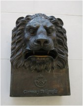 An iron lion-head mailbox on the front wall of the post office