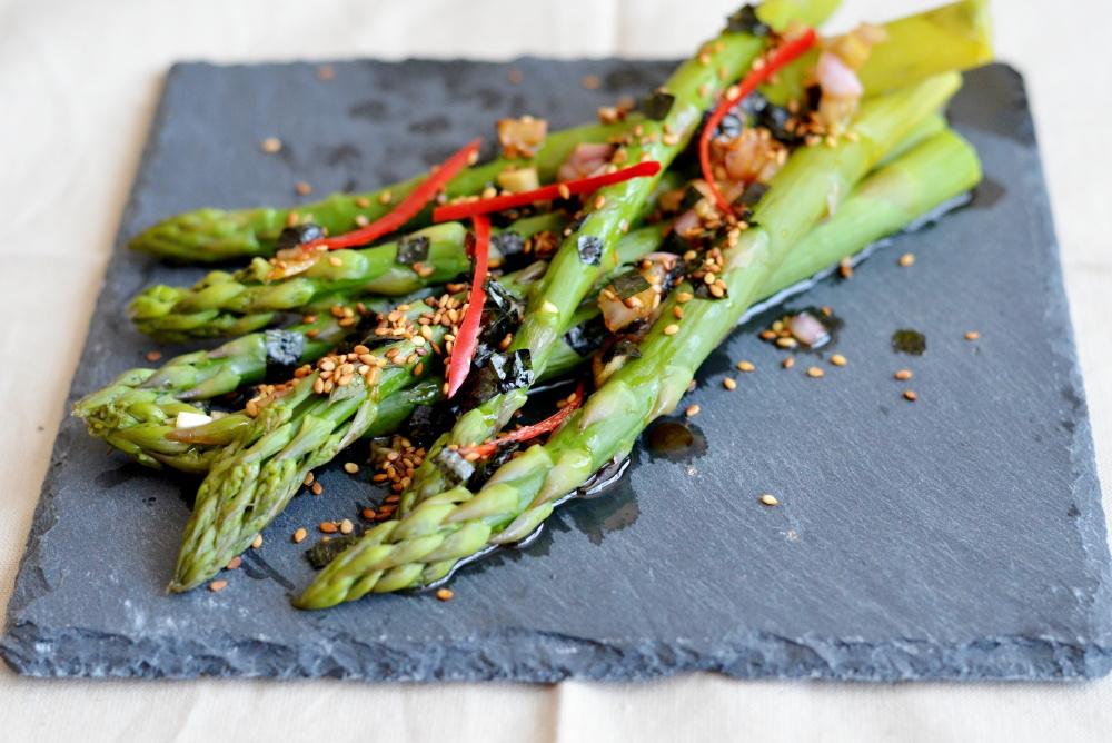 Salát ze zeleného chřestu je servírovaný se svěží a kyselejší zálivkou z rýžového octa, posypaný řasou nori, chili papričkou a opraženými sezamovými semínky