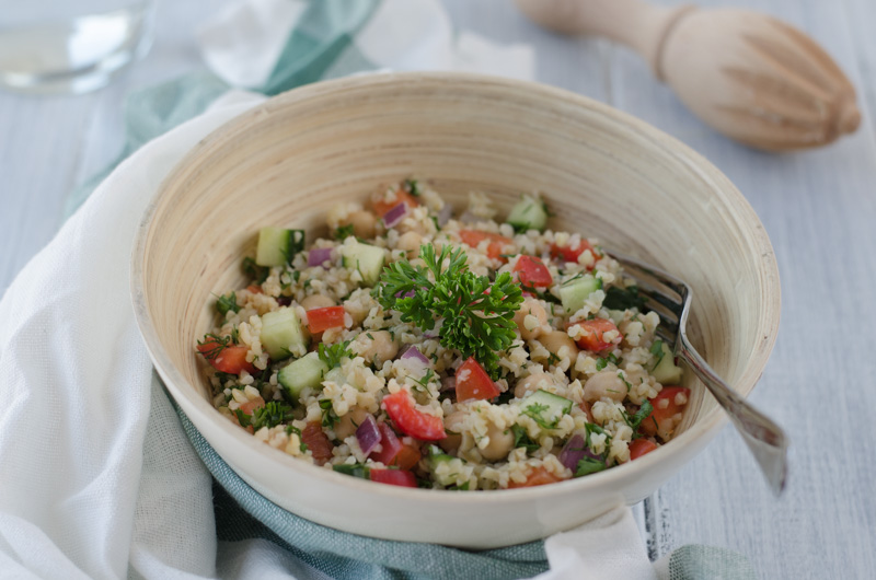 Light bulgur salad with cucumber, red pepper, chickpeas, and onion, seasoned with olive oil, garlic, lemon juice, and herbs is a fresh summer meal.