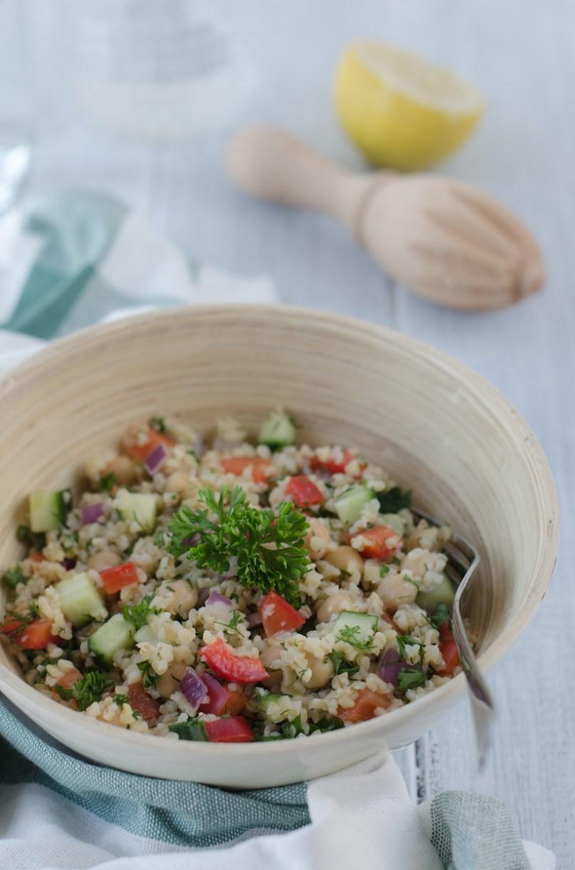 Lehký bulgurový salát s okurkou, paprikou, cizrnou a cibulkou ochucený olivovým olejem s česnekem, citronovou šťávou a bylinkami je osvěžující letní pokrm.