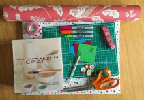 A photograph of various craft items, including craft cutting board, craft knife, Sharpie pens, paper and a craft book.