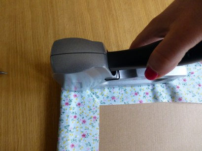 A photo showing Step 4, fixing the fabric to the board