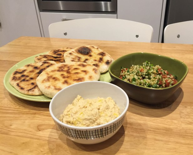 The flatbreads, hummus and tabbouleh on a dining table ready to eat