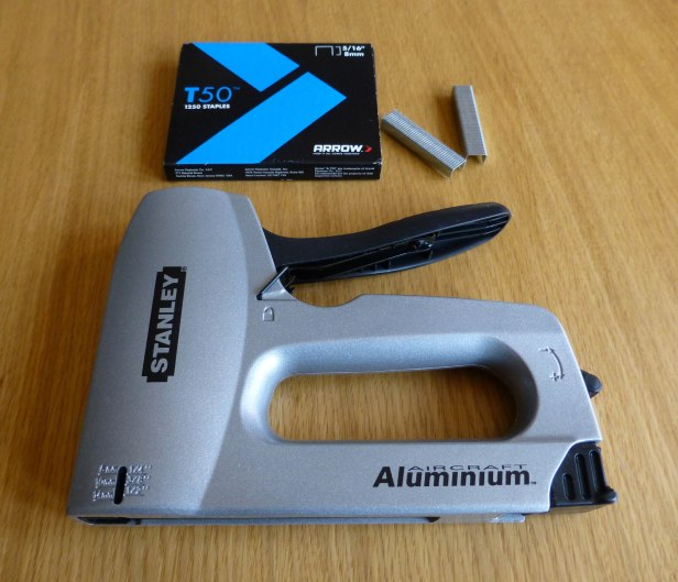 A photo of a Stanley staple gun and a box of staples