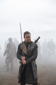 A photograph of Michael Fassbender as Macbeth ready to fight.
