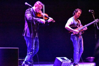 A photograph of musicians Holder & Smith playing the violin and guitar on stage