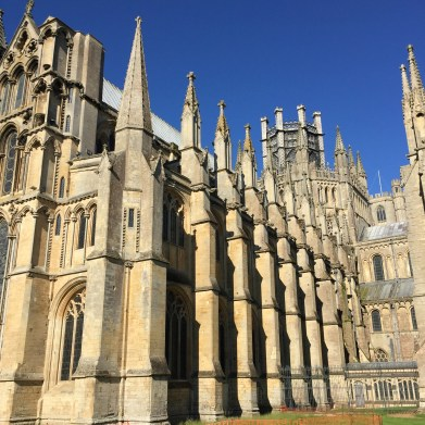 A photograph from low down at the eastern end of Ely Cathedral with brilliant blue sky above and shadow definition along the building
