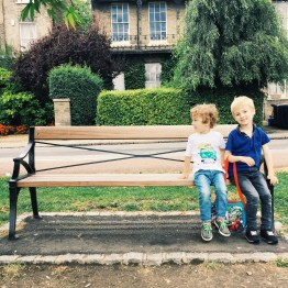 A photograph of Emma's children, Ben and Ollie, on a bench on Parker's Piece in Cambridge