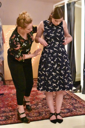 A photograph of Pippa wearing an Abigail style dress with aeroplane print. Aine points out the details.