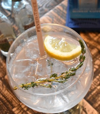 A top-down photograph of Emma's gin and tonic with a slice of lemon, sprig of thyme, wooden stirrer and lots of ice!