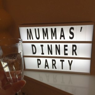 """A photograph of a lightbox saying """"Mummas Dinner Party"""" with Emma's glass of Prosecco in the left-hand corner"""
