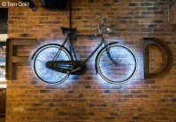 "A photograph of a bike suspended on a wall with its wheels back-lit and spelling ""OO"" in the word ""FOOD"". Photo by Tom Gold."
