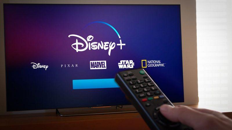 Controle remoto em frente a televisão com Disney Plus