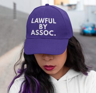"Woman with purple hair wearing purple ""Lawful by Assoc."" hat"