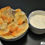 crispy potato chips in a dish next to dip