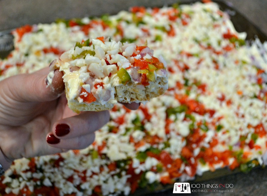 blogger's hand holding a slice of the veggie pizza
