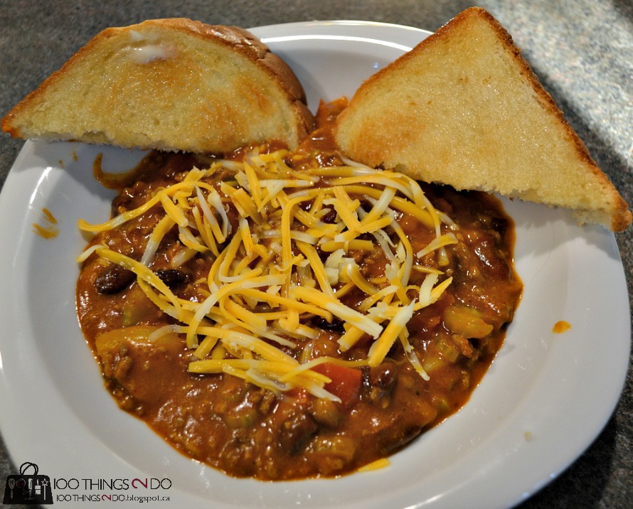 bowl of chili with toast and shredded cheese on top