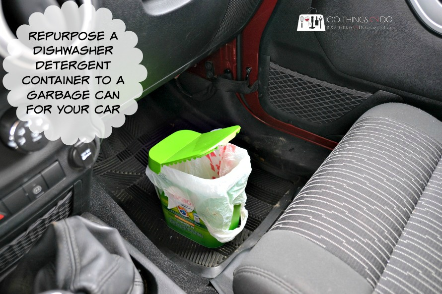 Dishwasher tablet container with grocery bag liner, sitting open on the floor of the car - looks like a mini garbage can