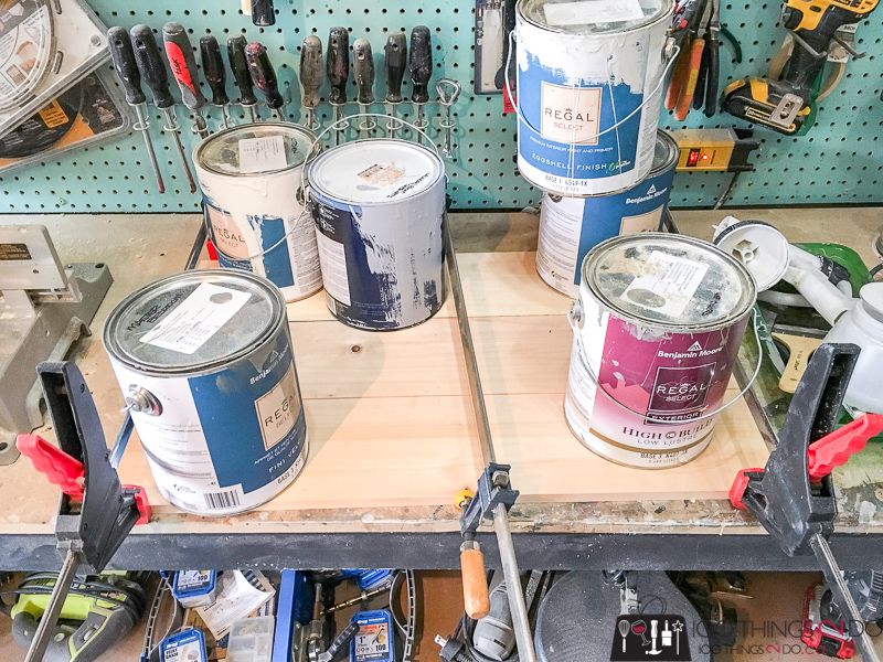 boards glued together, clamped and with paint cans as weights