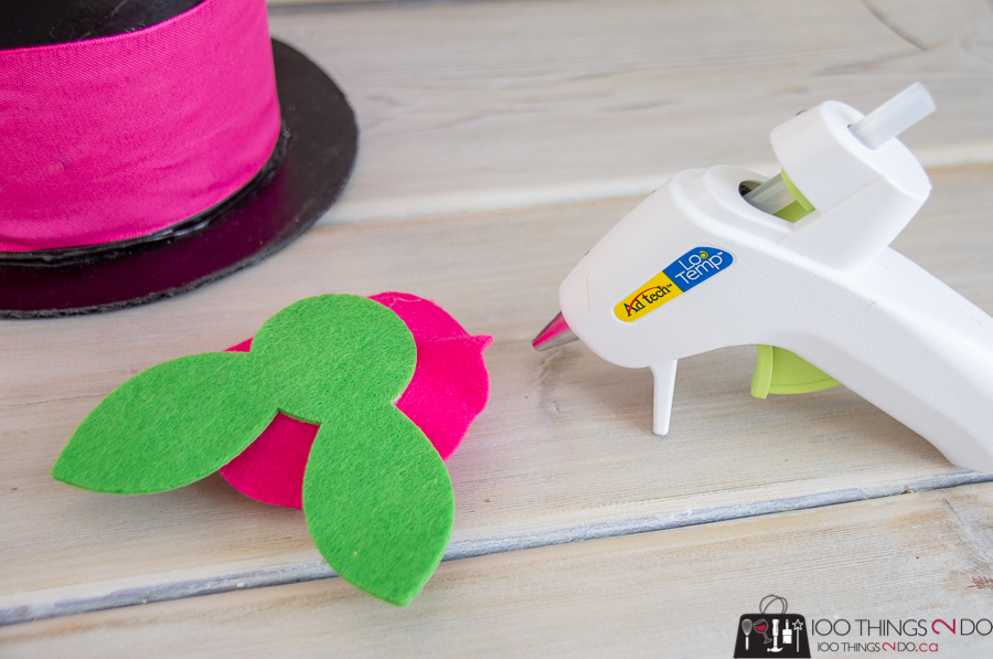 hot gluing a felt flower to a DIY top hat