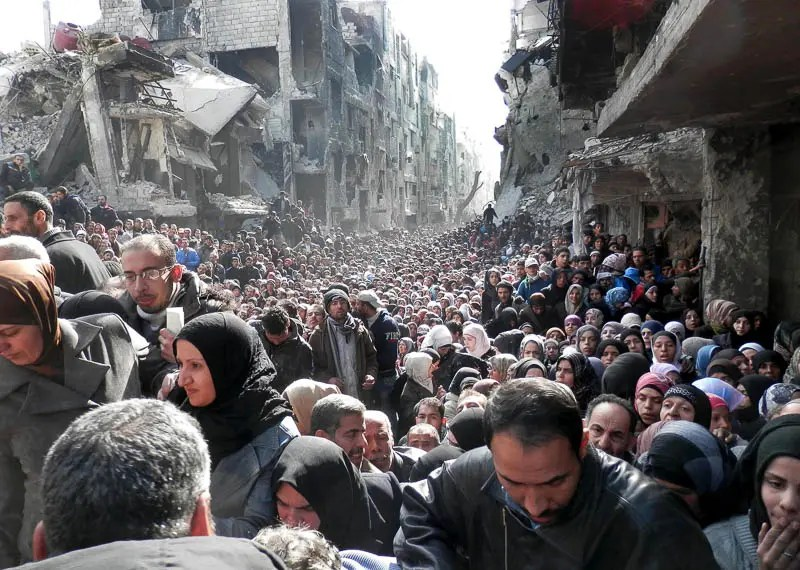 Palestinian refugees lining up for food aid in Syria – March 2014