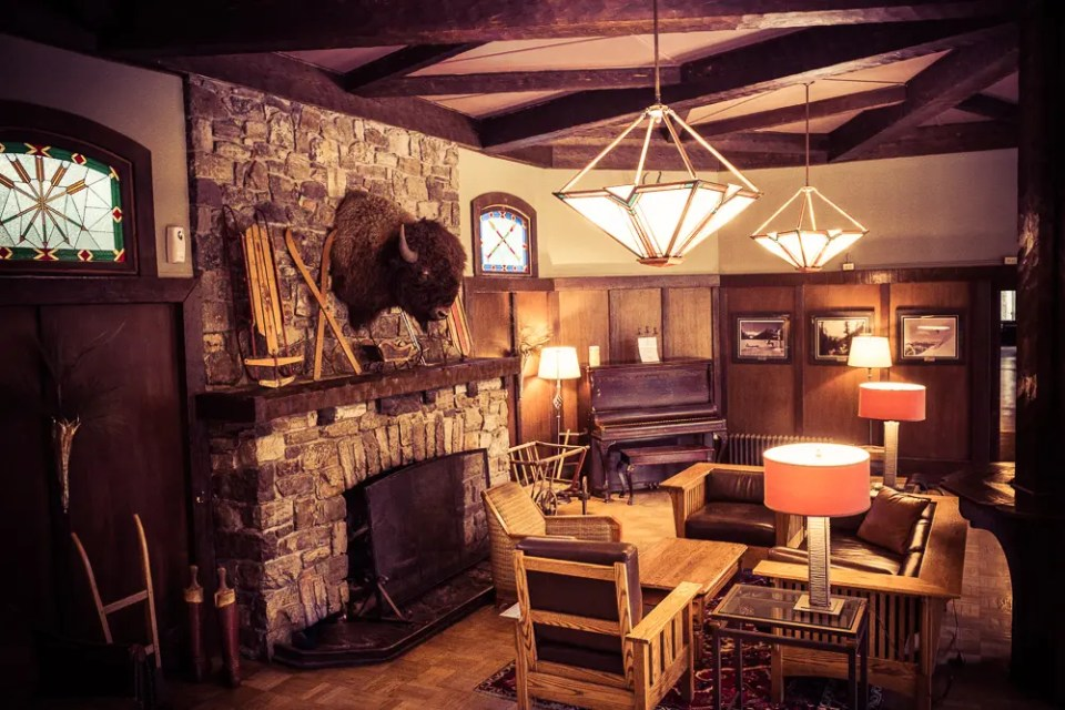 Deer lodge lounge with bison trophy, piano and fireplace
