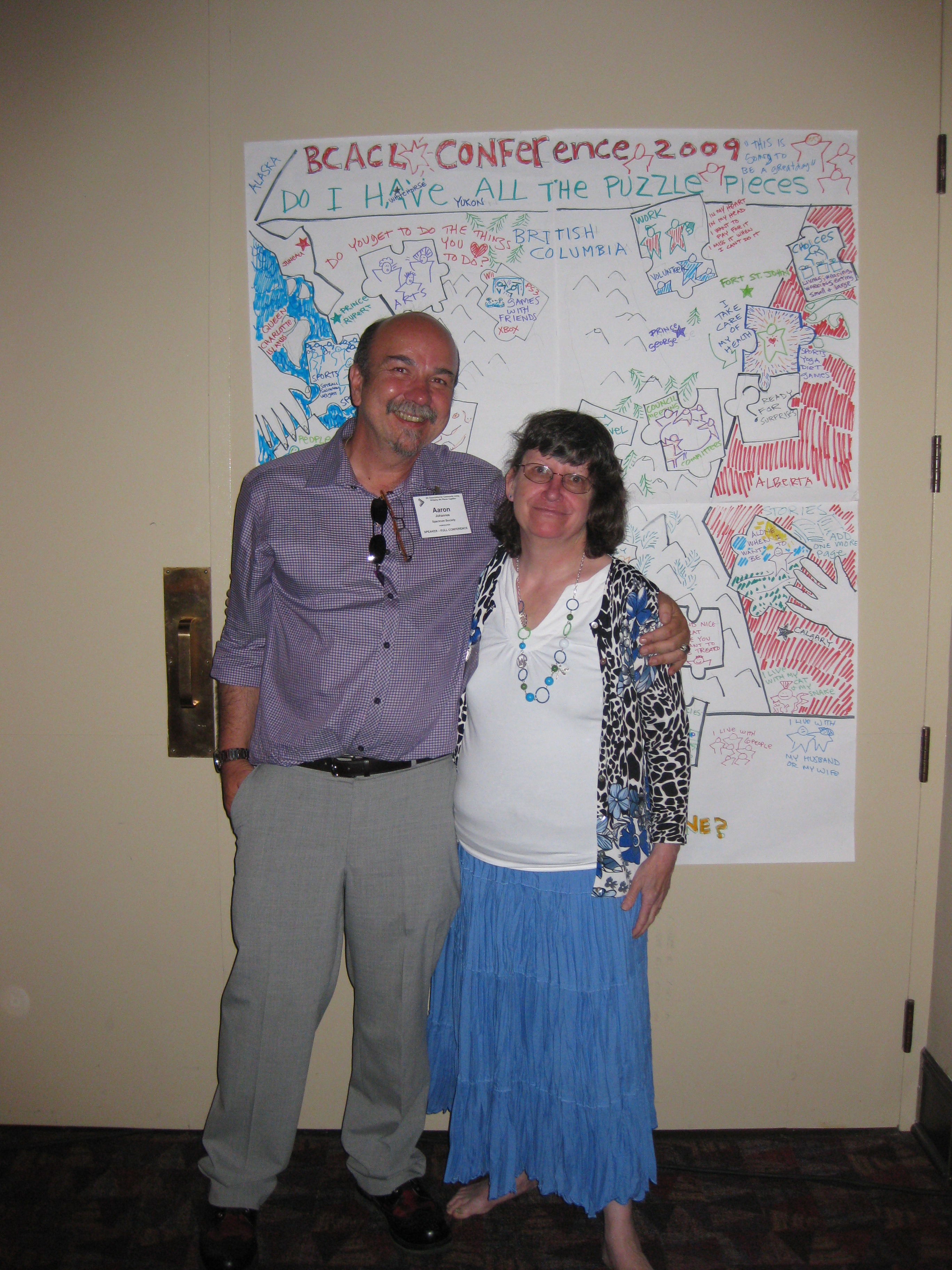 """Aaron and Barb Goode in front of the map of BC with """"parts of a good life"""" jig saw piece drawings"""