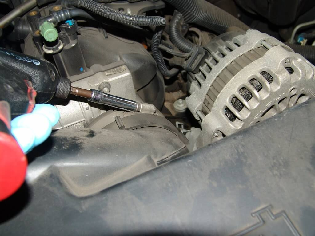 Disconnect the clip that holds the intake hose assembly to the radiator hose