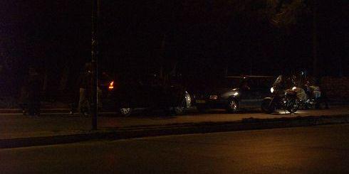 οι αστυνομικοί έχουν ακινητοποιήσει τον δράστη και τον καλούν να παραδοθεί, αυτός μένει μέσα στο δεξί αυτοκίνητο