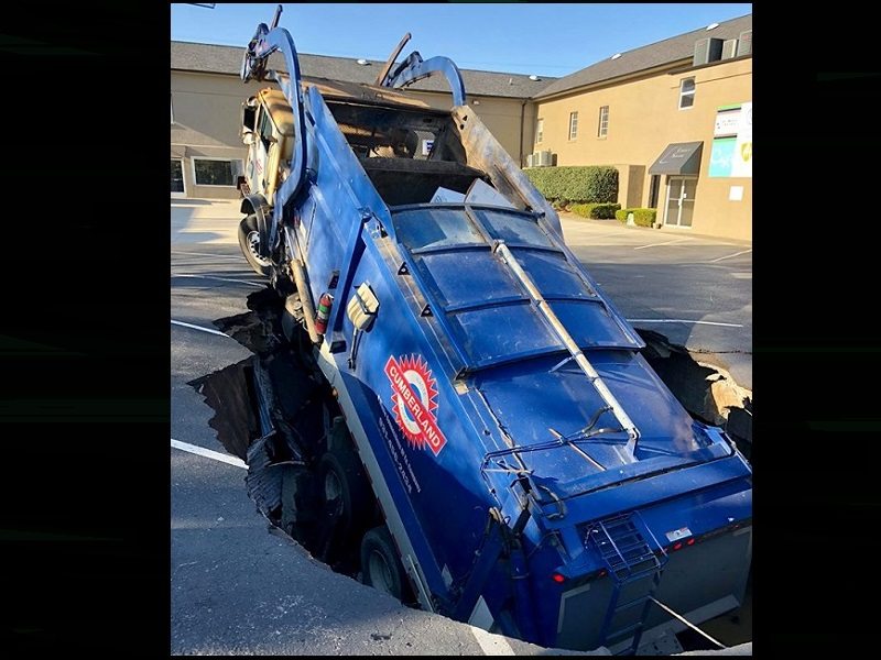 NO INJURIES REPORTED AFTER TRASH TRUCK DROPS INTO HOLE IN PARKING LOT