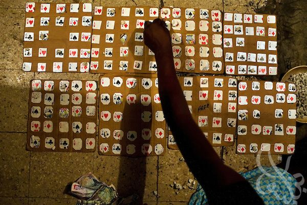 """A Jamaican woman uses small stones to mark numbers called during a game of ghetto bingo December 15, 2008 in the Rema garrison of Kingston, Jamaica. With an unemployment rate of more than 10% and a negative economic growth rate, opportunities are few for poor Jamaicans, known as """"sufferers"""", who try to make ends meet the best way they can."""