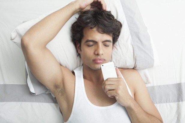man-lying-on-the-bed-holding-mobile-phone-y0umfobkctleff5kermlqa