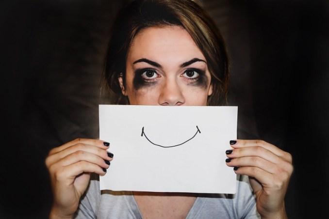 Une femme cachant ses pleurs sous un sourire factice pour gérer ses émotions
