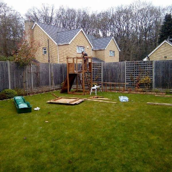 handyman building a Climbing frame with swing and slide set in garden
