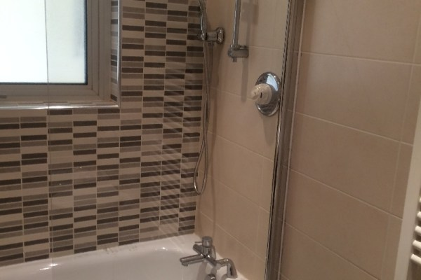 Tiled bathroom tub with shower screen