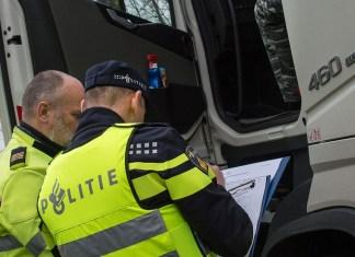 Papieren van trucker worden gecontroleerd door agenten