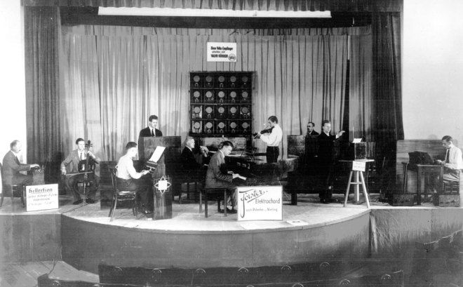"""Electric Concerts"" with the electroacoustic ""orchestra of the future"", 1932/1933 On the occasion of the 9th and 10th IFA in Berlin 1932 and 1933 for the first time found concerts with ""Electric Music"" instead. They played by the so-called ""Orchestra of the future"" all electroacoustic musical instruments then available. The ""Elektischen concerts"" made at the time an exceptional level of interest and broad support in the public, as the cooperating with private Theremingerät Erich Zitzmann-Zerini [second right] the engineer Gerhard Steinke told while gave him this original image. The orchestra consisted of two theremin instruments Trautonium [by Trautwein], Heller desk [of B. and P. Helberger Lertes], a neo-Bechstein grand piano [for suggestions of O. Vierling, S. Franco, W. Nernst and H . Driescher], Vierling piano [electro Acoustic piano by O. Vierling], electric violin, electric cello and Saraga generator [a light-electric device by W. Saraga, in principle, similar to the Theremingerät]. Photo: archive Gerhard Steinke"